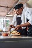 Kockar som tillsammans förbereder mat i restaurangkök royaltyfri bild