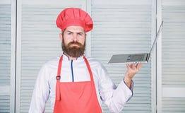 Kockb?rbar dator p? k?k Kulinarisk skola Hipster i hatt- och f?rkl?dek?pprodukter direktanslutet Shoppa online stiligt f?r bakgru arkivbilder