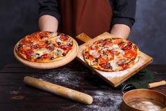 Kockbagaren i förklädeinnehav stiger ombord med varm nytt bakad pizza royaltyfria foton
