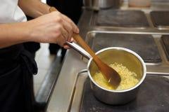 Kocken är matlagningrisotto Royaltyfri Fotografi