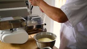 Kocken använder en bitande maskin för pasta för att göra ny spagetti arkivfilmer