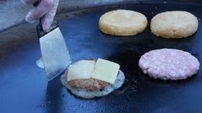 Kocken använder en slagfackla för att smälta ost på en köttkotlett Kocken smälter ost på en hamburgare genom att använda en slagf arkivfilmer