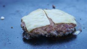 Kocken använder en slagfackla för att smälta ost på en köttkotlett Kocken smälter ost på en hamburgare genom att använda en slagf lager videofilmer