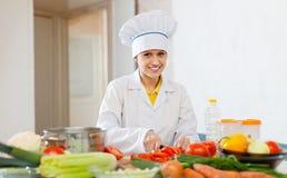 Kocken arbetar med grönsaker på kommersiellt kök Arkivfoton