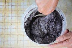 Kocken blandar äggvitor med vallmofrön för att förbereda en kaka arkivfoton