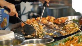 Kocken förbereder ett smaskigt block som är thailändskt med smaklig stekt räka på ett öppet, wokar på den asiatiska marknaden för stock video
