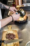 Kocken förbereder fläskkarrén för nötköttbiff i restaurangköket royaltyfria bilder