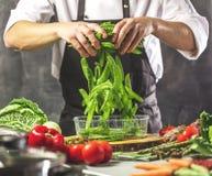 Kocken förbereder grönsaker för att laga mat i restaurangköket royaltyfri bild
