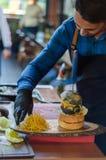 Kocken förbereder hans hamburgare för service fotografering för bildbyråer