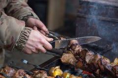 Kocken förbereder kött på steknålen Arkivfoto