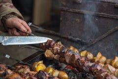 Kocken förbereder kött på steknålen Royaltyfri Foto
