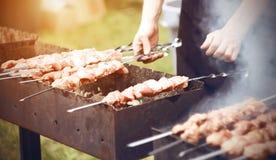 Kocken f?rbereder kebaber p? gallret i sommaren royaltyfri foto