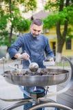 Kocken förbereder musslor i en stor stekpanna på gatan Royaltyfri Foto