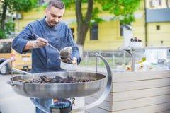 Kocken förbereder musslor i en stor stekpanna på gatan Arkivfoto
