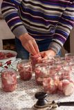 Kocken förbereder pre-hus beskydd En man sätter stycken av rått kött i glass krus royaltyfri fotografi
