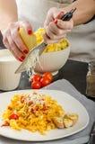 Kocken förbereder tagliatelle med vitlök och körsbärsröda tomater arkivbild