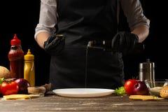Kocken förbereder yttersidan, genom att hälla smör för nötköttsmå pastejer, med ingredienser på bakgrunden, restaurangaffären, fa arkivfoton