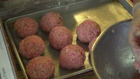 Kocken förlägger rå köttbullar på en panna lager videofilmer
