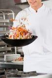 Kocken Flipping Vegetables wokar in Arkivfoton