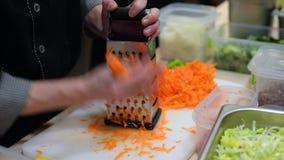 Kocken gnider morötter på rivjärnet arkivfilmer