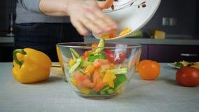 Kocken häller in ingredienser för en bunkesallad stock video