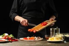 Kocken häller körsbärsröda tomater i en platta Frost i rörelse För att förbereda pizza, tomatsås, sallad Läckert matbegrepp som l royaltyfri fotografi