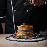 Kocken häller lönnsirap på pannkakabunt med blåbär och jordgubbar på svart bakgrund Arkivfoton