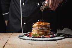 Kocken häller lönnsirap på pannkakabunt med blåbär och jordgubbar på svart bakgrund Royaltyfria Foton