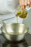 Kocken häller olja in i pannan för att laga mat för matlagningmat för serie fulla recept Arkivfoto
