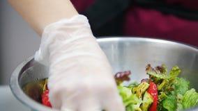 Kocken häller såsen över salladen i bunke, i ramen av händer av kocken arkivfilmer