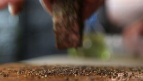 Kocken häller svartpeppar förser med rutor ut nötköttbiff arkivfilmer