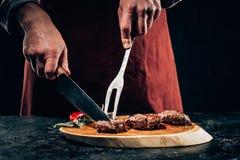 Kocken i förkläde med köttgaffeln och kniv som skivar gourmet, grillade biffar med rosmarin och chilipeppar på träbräde arkivfoto