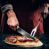 Kocken i förkläde med köttgaffeln och kniv som skivar gourmet, grillade biffar med rosmarin och chilipeppar på träbräde Royaltyfri Bild