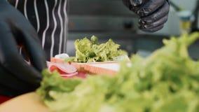 Kocken i restaurang lagar mat en smörgås med grönsallat, skinka och ost lager videofilmer