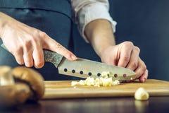 Kocken i svart förkläde klipper vitlöken med en kniv Begrepp av eco-vänskapsmatch produkter för att laga mat royaltyfri bild