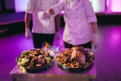 Kocken kött hällde alkohol och uppsättningbrand till royaltyfri foto