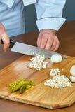 Kocken klipper champignons för framställning en geléhöna av den fulla samlingen av kulinariska recept Arkivfoto