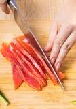 Kocken klipper den röda fisken med en kniv royaltyfria bilder