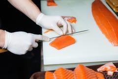 Kocken klipper den röda fisken med kniven på den vita skärbrädan Kockmatlagningmat på köket Sushi arkivbild