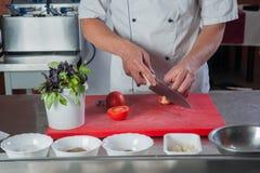 Kocken klipper en tomat med en kniv på köket Arkivfoto