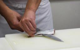 Kocken klipper fisken in i stycken av sushi (11) Arkivfoto