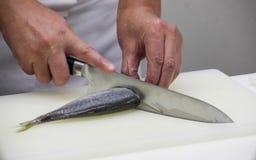 Kocken klipper fisken in i stycken av sushi Arkivfoto