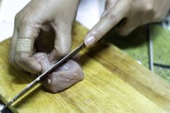 Kocken klipper griskött på kvarteret royaltyfria foton