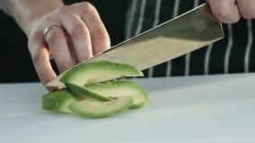Kocken klipper halvan av avokadot in i skivor Slowmotion lager videofilmer