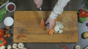 Kocken klipper lökar och morötter Lökar och morötter som en ingrediens för framställning av soppa eller andra maträtt Top beskåda stock video