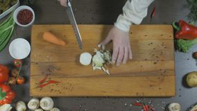 Kocken klipper lökar och morötter Lökar och morötter som en ingrediens för framställning av soppa eller andra maträtt Top beskåda arkivfilmer