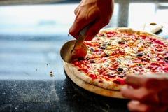 Kocken klipper smaskig pizza, genom att använda pizzaskäraren för att avskilja den för kund i kök på pizzeria arkivbilder