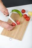 Kocken klipper tomaten på ett bräde Royaltyfri Bild