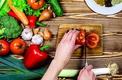 Kocken klippte en skiva av nya tomatsallader Därefter på träyttersidor är nya grönsaker och kryddor Arkivfoton