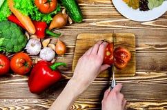 Kocken klippte en skiva av nya tomatsallader Närliggande är nya grönsaker och kryddor Royaltyfri Foto
